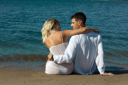 backview of romantic slavonic couple - blonde girl in peignoir and brown haired man in white shirt taking their time on the beach photo