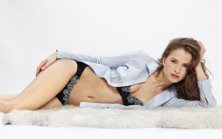 black woman lingerie: portrait of beautiful caucasian model posing on white furs in blue shirt and lingerie