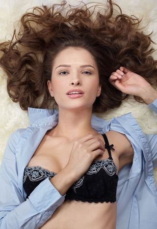 portrait of beautiful caucasian model posing on white furs in blue shirt and lingerie photo