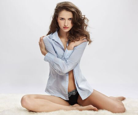 woman lingerie: portrait of beautiful caucasian model posing on white furs in blue shirt and lingerie