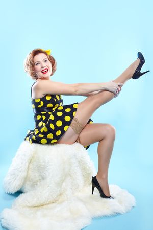 portrait of girl dressed and maked up in retro style posing on white fur photo