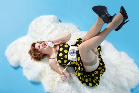 portrait of girl dressed and maked up in retro style posing on white fur with old-style telephone photo