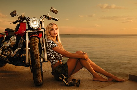 young beautiful blonde outdoors, posing with red motorcycle on quay photo