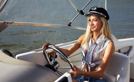 young beautiful blonde in captains hat outdoors, posing on yacht photo
