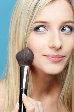 slavonic: portrait of beautiful slavonic blonde girl making up on blue