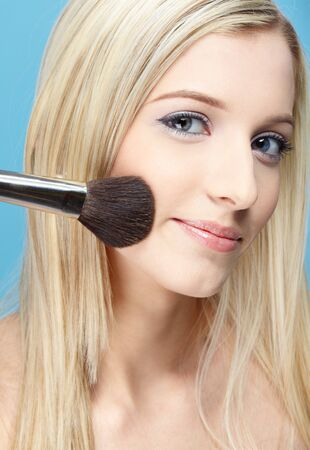 portrait of beautiful slavonic blonde girl making up on blue photo