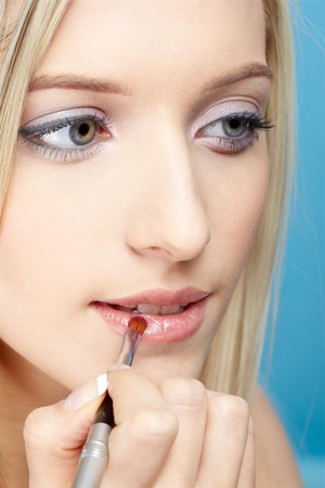 portrait of beautiful slavonic blonde girl making up on blue Stock Photo - 7105066
