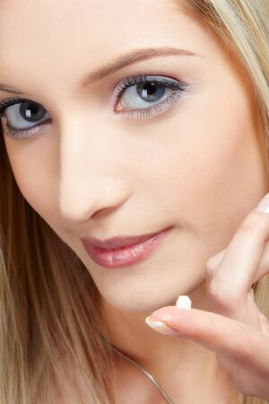closeup portrait of beautiful slavonic blonde girl with a drop of cream on her finger photo
