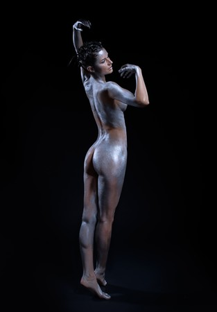 portrait of nude girl body painted with silver posing on black photo