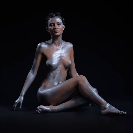 portrait of nude girl body painted with silver sitting on black Stock Photo - 7092595