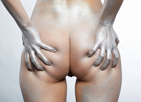 nude girl squeezing her buttocks painted with silver photo