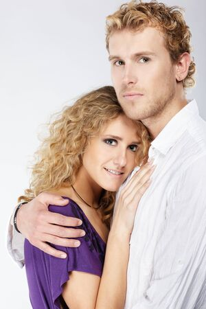 portrait of blonde curly couple on gray photo