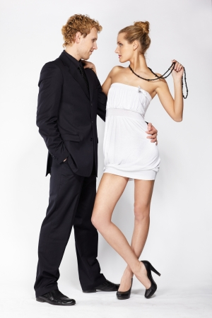 portrait of well-dressed blonde couple on gray.