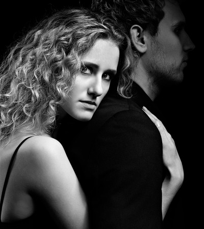 portrait of couple - blonde girl embraces man from behind. mans face in dark photo
