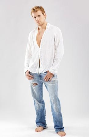 portrait of blonde man in white shirt posing on gray photo