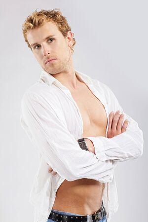 Portrait d'un homme blond en chemise blanche posant sur gris