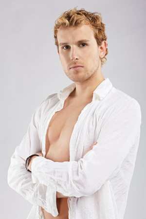 portrait of blonde man in white shirt posing on gray photo