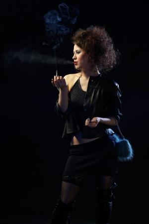 portrait of girl dressed like hooker smoking on black photo