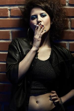 portrait of girl dressed like hooker posing near brick wall photo