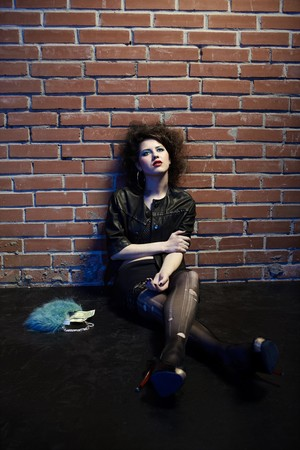fishnets: portrait of girl dressed like hooker posing near brick wall