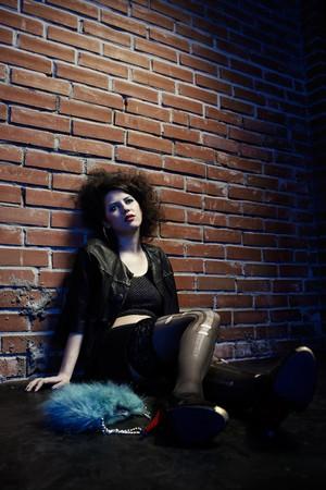 hooker: portrait of girl dressed like hooker posing near brick wall