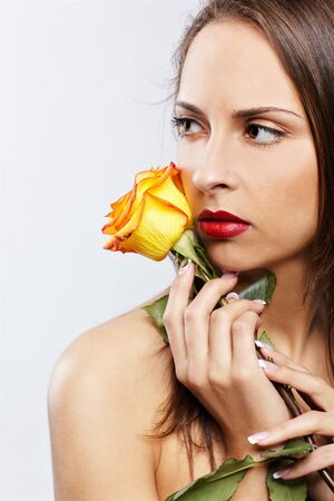 portrait of brunette girl posing with yellow rose photo