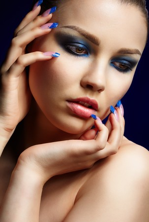 Close-up portrait of beautiful brunette with blue eye shadow make up and manicure photo