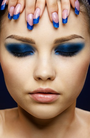 closed eye: Close-up portrait of beautiful brunette with blue eye shadow make up and manicure