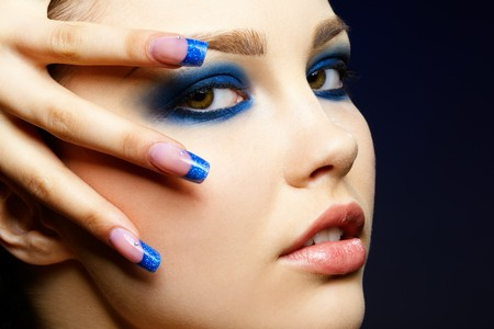 Close-up portrait of beautiful brunette with blue eye shadow make up and manicure Stock Photo - 7359033