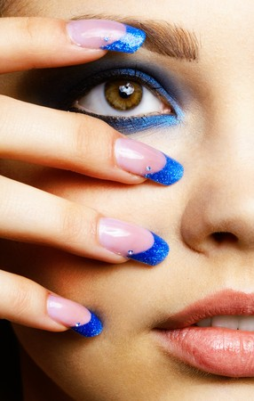 nails: Close-up portrait of beautiful brunette with blue eye shadow make up and manicure