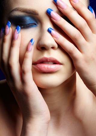 finger to lips: Close-up portrait of beautiful brunette with blue eye shadow make up and manicure