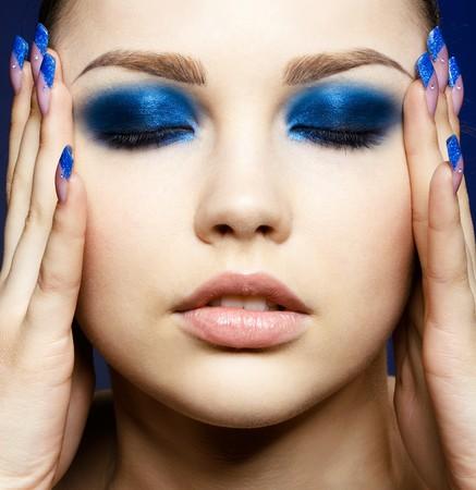 ojos cerrados: Retrato de Close-up de hermosa morena con la sombra de ojos azul conforman y manicura  Foto de archivo
