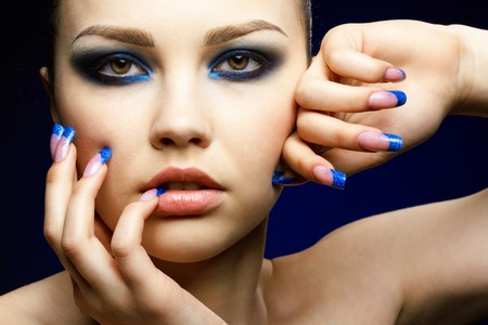 woman face close up: Close-up portrait of beautiful brunette with blue eye shadow make up and manicure