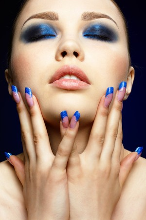 nailart: Close-up portrait of beautiful brunette with blue eye shadow make up and manicure