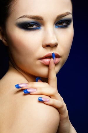 quiet adult: close-up portrait of beautiful brunette with blue eye shadow make up and manicure Stock Photo
