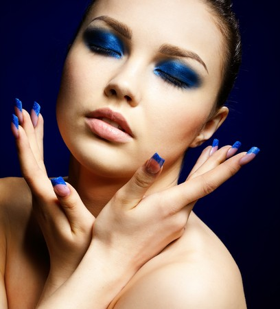 closed eye: close-up portrait of beautiful brunette with blue eye shadow make up and manicure Stock Photo