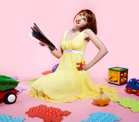 portrait of redhead woman reading magazine and speaking on phone with various toys around photo