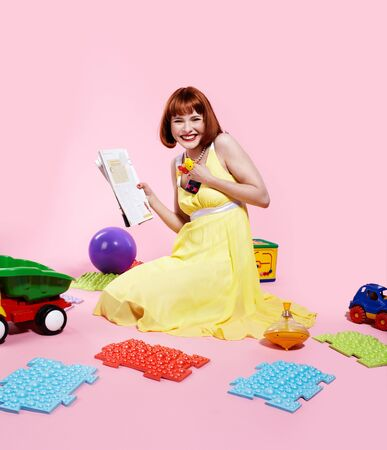 portrait of redhead woman reading magazine with various toys around photo