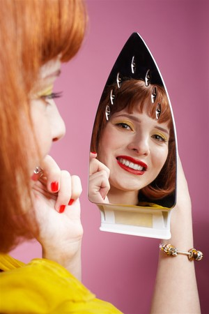 checking in: portrait of redhead woman looking at her reflection in iron and checking in her make-up