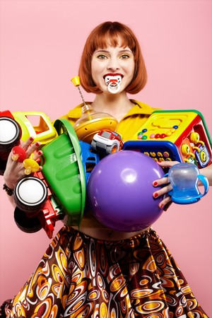 portrait of redhead woman posing with various toys on pink photo