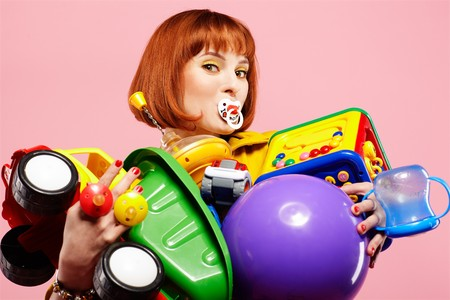 adult toys: portrait of redhead woman posing with various toys on pink