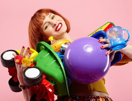 portrait of redhead woman posing with various uncopirighted toys on pink background photo