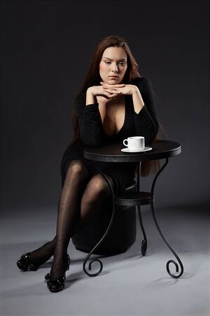 portrait of beautiful girl sitting at the elegant cafe table with a cup of coffee photo