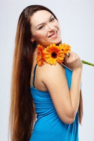portrait of beautiful girl posing with gerbera on white photo