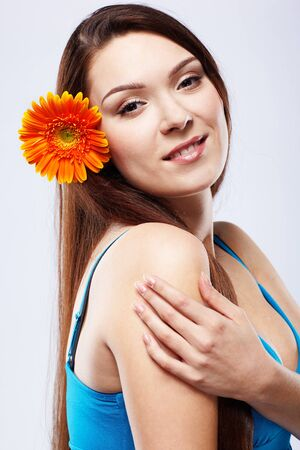 portrait of beautiful girl posing with gerbera flower in her hair photo