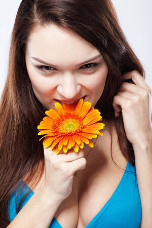 portrait of beautiful girl jokingly biting gerbera flower on white photo