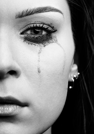 to cry: close-up portrait of beautiful crying girl with smeared mascara Stock Photo