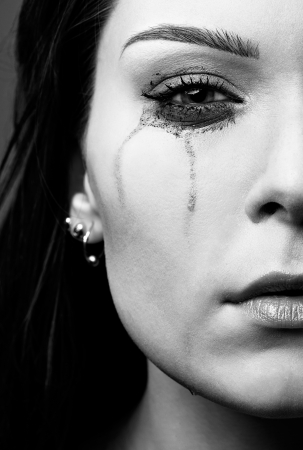 close-up portrait of beautiful crying girl with smeared mascara photo