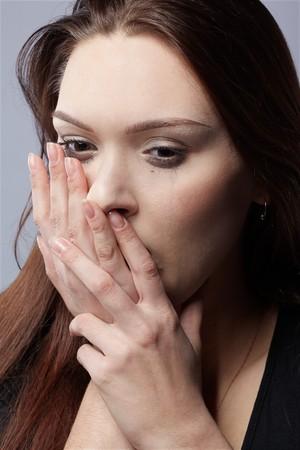 portret van prachtige huilend meisje met vlekkerig mascara verbergen haar gezicht in handen  Stockfoto