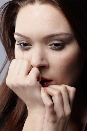 portrait of beautiful crying girl with smeared mascara hiding her face in hands Stock Photo - 7419213